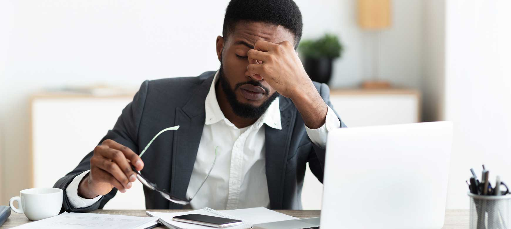 Man in front of computer with hands to his forehead looking worn out